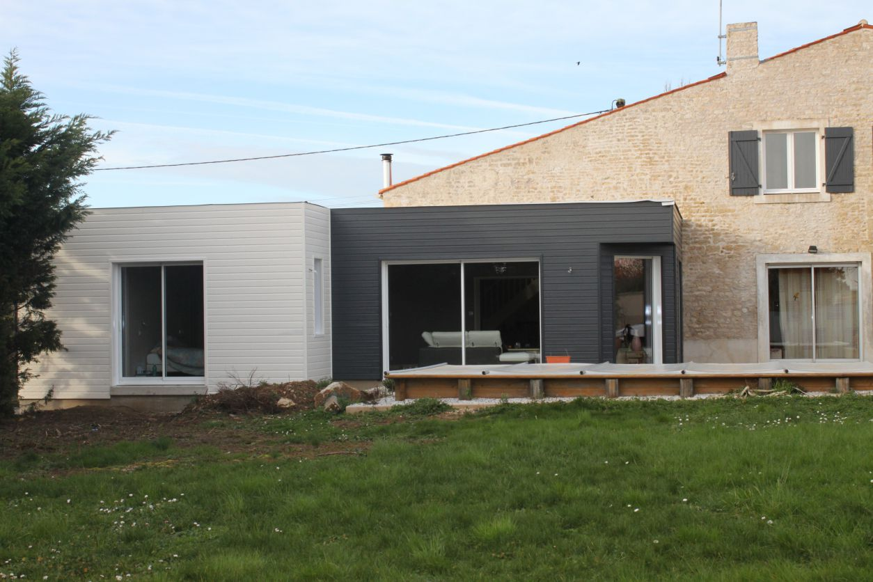 Extension contemporaine en toit plat sur une maison en pierres